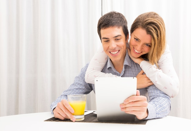 Woman embracing her boyfriend from behind looking at digital tablet holding juice