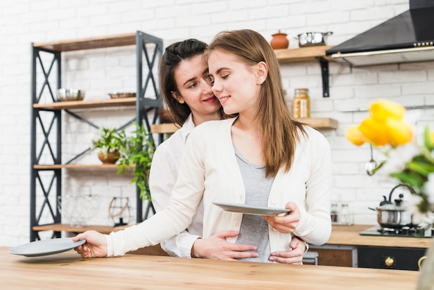 Woman embracing her girlfriend from behind arranging the ceramic plates on table