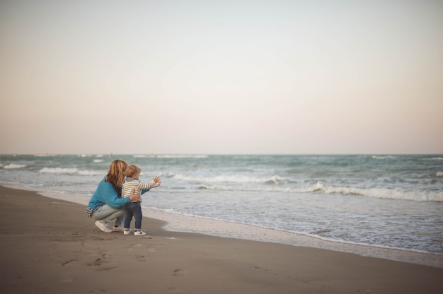 Woman embracing her son while looking at the sea