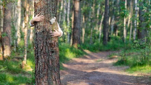 포용 / 포옹 나무 줄기, 숲에서 야생화를 손에 들고 여자. 에코 관광
