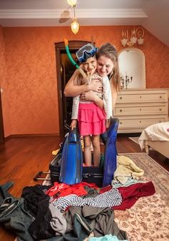 スーツケースの中に立っているマスクとシュノーケルで小さな女の子を抱きしめる女性