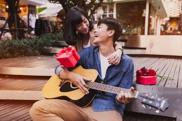 Woman embracing a man and holding a gift while he plays the guitar