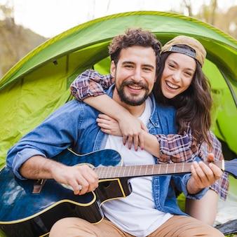 Woman embracing man with guitar