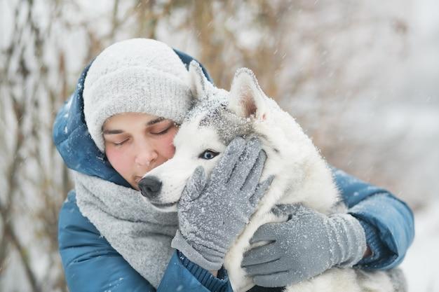 冬に雪に覆われたシベリアンハスキーを抱きしめる女性