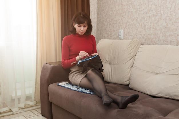 十字架の女性の刺繡は、リビングルームのソファに座っています
