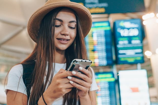 Woman emphatically looks at the phone with airport scoreboard