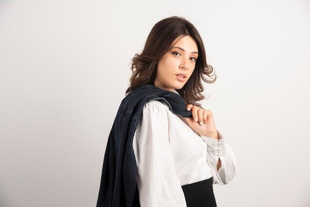 Impiegata della donna che tiene la sua giacca sopra le spalle.