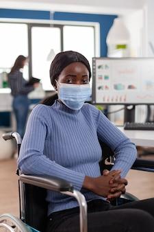 正面を向いているコロナウイルスに対する保護マスクを持つ障害を持つ女性従業員