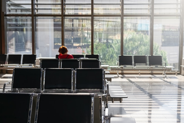 Woman in empty waiting hall at airport or train station on sunny day.