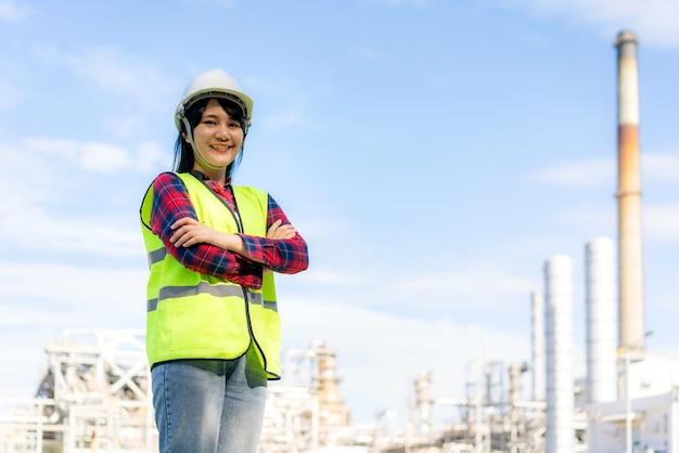 Женщина инженер скрестила руку и уверенно улыбалась