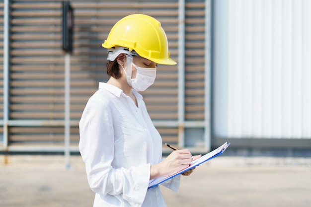 Woman engineer check building report, writing a technical report about the manufacturing process.