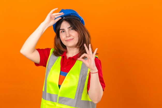 Woman engineer in construction vest and safety helmet looking confident making greeting gesture touching helmet doing ok sign over isolated orange wall