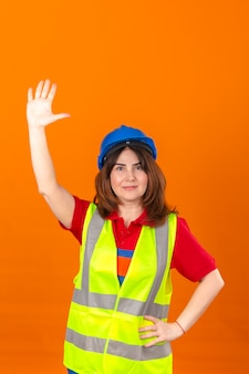 Woman engineer in construction vest and safety helmet with smile waving to someone with hand over isolated orange wall