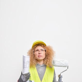 불행한 표정으로 머리 위로 집중하는 여성 엔지니어는 청사진을 들고 있고 롤러는 안전모 유니폼을 입는다