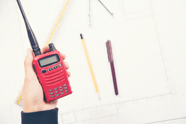 Woman engineer hold radio in hand at construction site.
