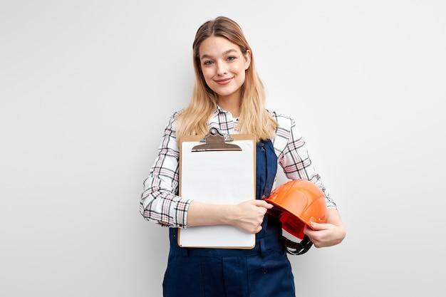 Женщина-инженер, держащая бумажную таблетку и шлем, одетая в униформу комбинезона построителя и смотрящую на камеру изолированную над белой предпосылкой студии.