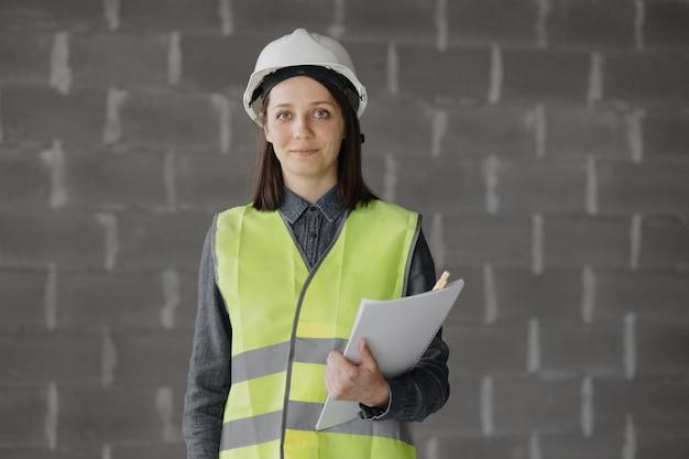 건설 현장에서 흰색 헬멧과 안전 조끼를 입은 여성 엔지니어