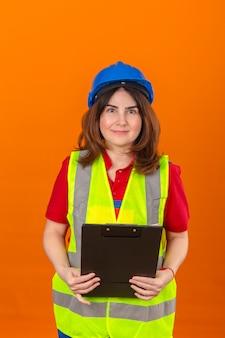 孤立したオレンジ色の壁に立っている顔に笑顔で自信を持って探している手でクリップボードを保持している建設ベストと安全ヘルメットの女性エンジニア
