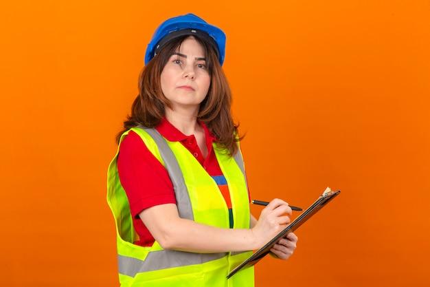 孤立したオレンジ色の壁の上に自信を持って誇りに思って立っているを探している手でペンでクリップボードを保持している建設ベストと安全ヘルメットの女性エンジニア