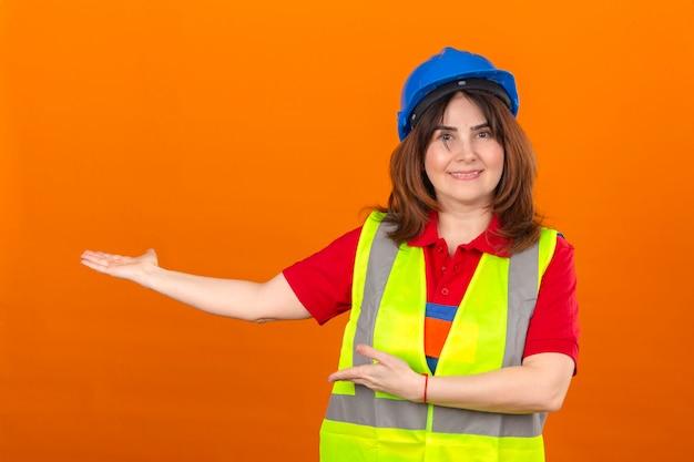 建設ベストと安全ヘルメットを提示し、孤立したオレンジ色の壁に顔に笑顔でカメラを見て手の手のひらで指している女性エンジニア