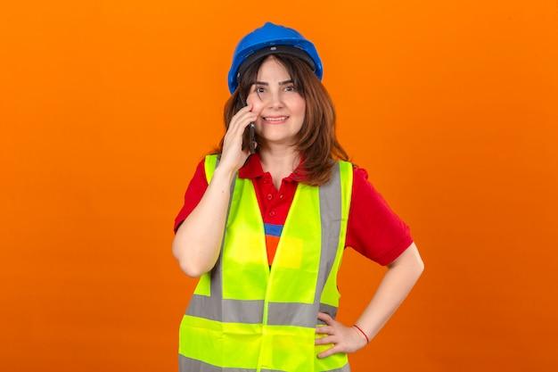 Женщина-инженер в строительном жилете и защитном шлеме разговаривает по мобильному телефону, весело улыбаясь, стоя над изолированной оранжевой стеной