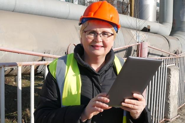 Женщина-инженер в каске с ноутбуком, крупным планом
