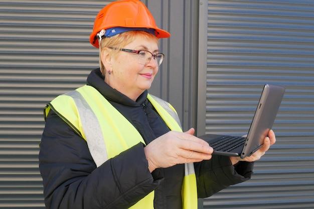 倉庫の背景にラップトップとハード帽子の女性エンジニア