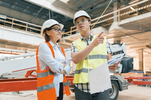 Woman engineer and man builder at construction site