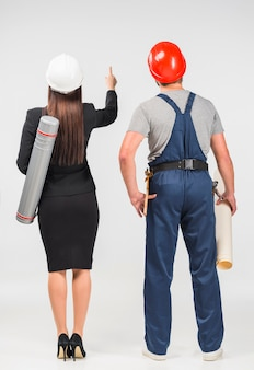 Woman engineer standing with builder pointing up