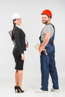 Woman engineer standing with builder smiling