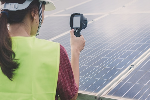 Woman engineer using thermal imager to check temperature heat of solar panel
