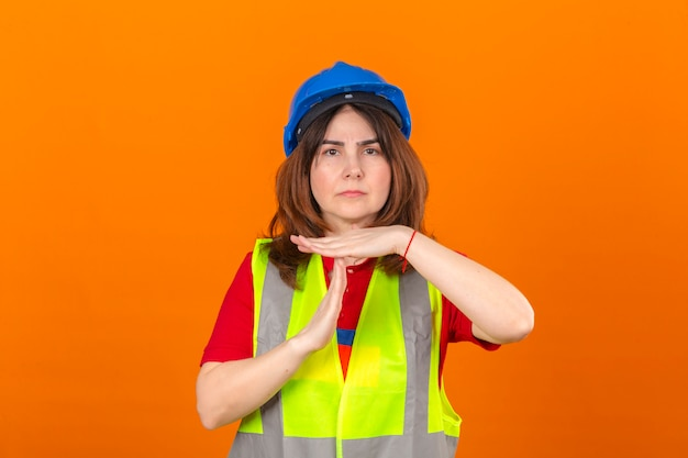 孤立したオレンジ色の壁を越えて不満と深刻な顔の手でタイムアウトジェスチャーを行う建設ベストと安全ヘルメットを身に着けている女性エンジニア