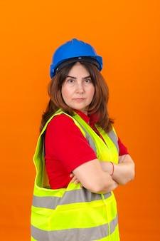分離のオレンジ色の壁に深刻な顔をして腕を組んで横に立っている建設ベストと安全ヘルメットを身に着けている女性エンジニア