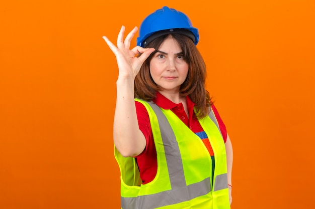 分離のオレンジ色の壁の上に立っているokサインをやっている自信を持って笑顔で建設ベストと安全ヘルメットを身に着けている女性エンジニア