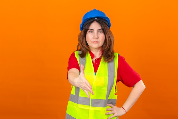 Женщина-инженер в строительном жилете и защитном шлеме с серьезным лицом предлагает руку, делая приветственный жест над изолированной оранжевой стеной