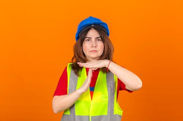 Maglia d'uso della costruzione dell'ingegnere della donna e casco di sicurezza che fanno gesto di timeout con il fronte frustrato e serio delle mani sopra la parete arancio isolata
