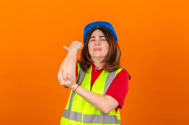 Woman engineer wearing construction vest and safety helmet looking unwell touching elbow having pain standing over isolated orange wall