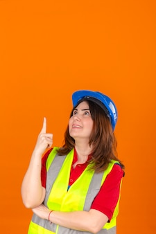 Woman engineer wearing construction vest and safety helmet looking up pointing to something with smile on face over isolated orange wall