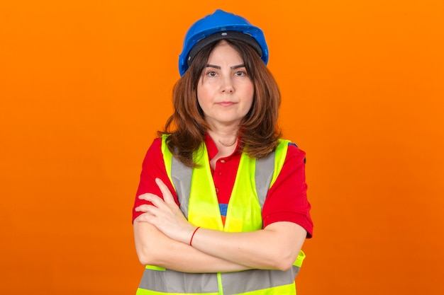 Woman engineer wearing construction vest and safety helmet standing with arms crossed with serious face over isolated orange wall