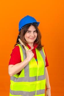 Maglia d'uso della costruzione dell'ingegnere della donna e casco di sicurezza che stanno con il martello sulla spalla con il sorriso sul fronte sopra la parete arancio isolata