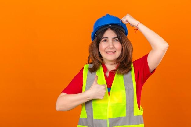 La maglia d'uso della costruzione dell'ingegnere della donna e il casco di sicurezza sorpresi con la mano sulla testa per l'errore ricordano l'errore che mostra il pollice su che sembra confuso sopra la parete arancio isolata