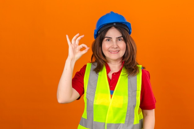 Woman engineer wearing construction vest and safety helmet with big smile on face doing ok sign standing over isolated orange wall