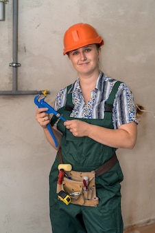 Woman engineer with tool belt and adjustable key