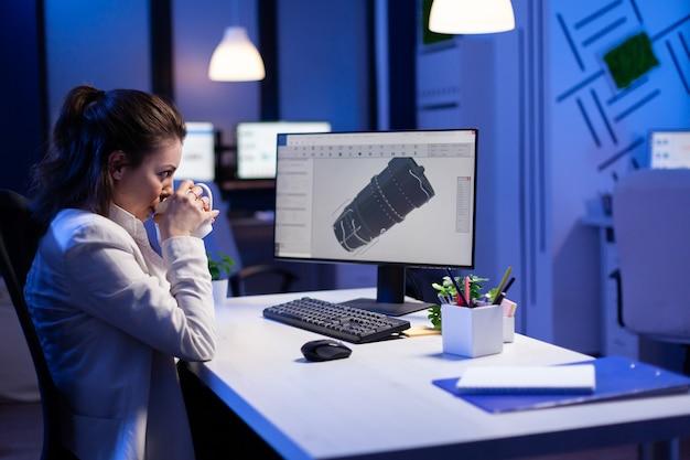 컴퓨터 앞에서 커피를 마시는 동안 산업 터빈의 3d 모델에서 밤 늦게 일하는 여성 엔지니어
