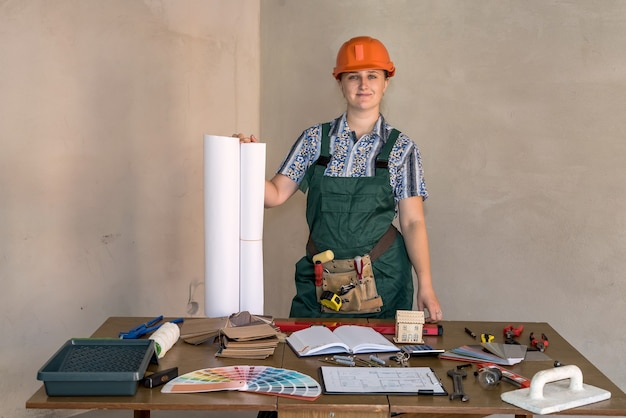 Woman engineer at working place with blueprints