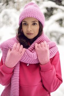 여자는 분홍색 옷을 입고 니트 스카프와 모자를 겨울에 눈 덮인 숲에 서서 즐길 수 있습니다.