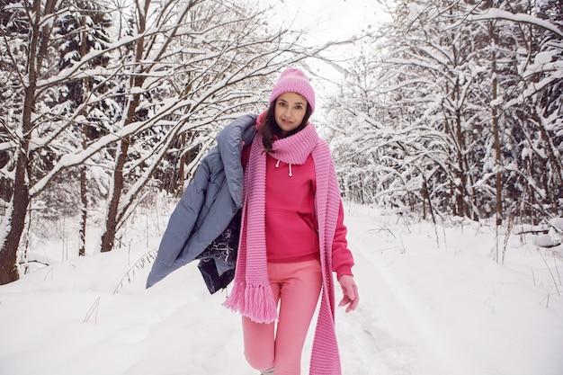 女性はピンクの服でジャケット、ニットのスカーフ、帽子は冬の雪の森に立って楽しむ