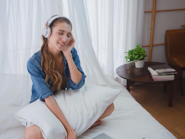 여자는 집에서 음악을 듣고 즐길, 여자는 침대에서 음악을 듣고 휴식을