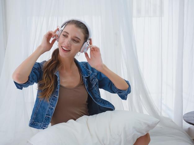 여자는 집에서 음악을 듣고 즐길, 여자는 침대에서 음악을 듣고 휴식을 프리미엄 사진