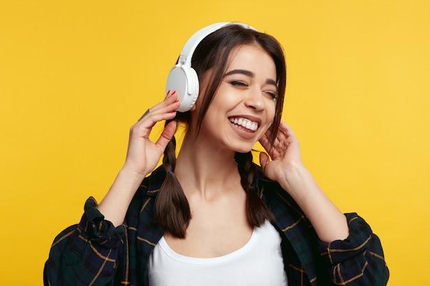 Женщина наслаждается звуком музыки, закрывает глаза, слушает песню у желтой стены